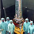 crew poses with spacecraft, inspection